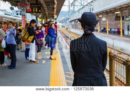 KYOTO JAPAN - NOVEMBER 23 2015: Unidentified Japanese train conductor is on her duty on a local train platform
