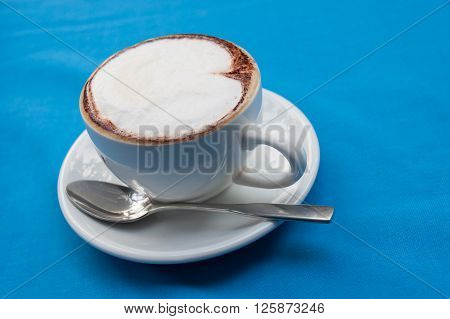 Hot Cappucino coffee on blue background .