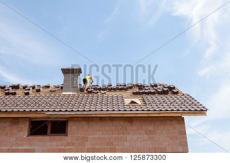 Roofing: construction worker on a roof covering it with tiles - roof renovation: installation of tar paper new tiles and chimney