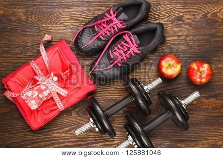 Pair of sneakers measuring tape dumbbells and apple wooden background