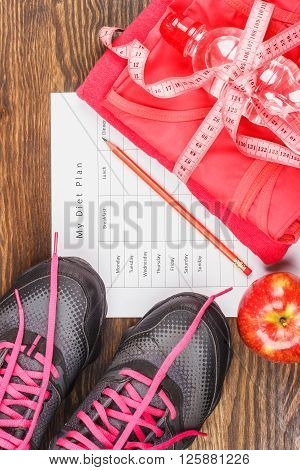 Sport items measuring tape and apple wooden background