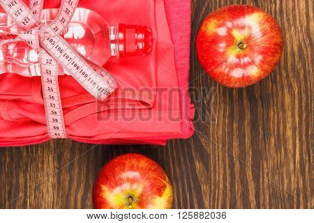 Sport clothing measuring tape and bottle wooden background