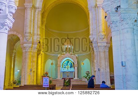 JERUSALEM ISRAEL - FEBRUARY 16 2016: The white prayer hall of Church of Our Lady of the Spasm decorated with high stone columns and altar on February 16 in Jerusalem.