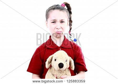Little sick girl with thermometer embraces toy bear