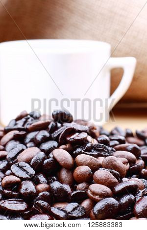 cup of coffee with coffee beans on brown jute fabric