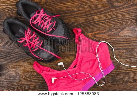 Pair of sneakers headphones and sports bra wooden background