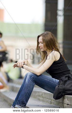 Young woman look at clock