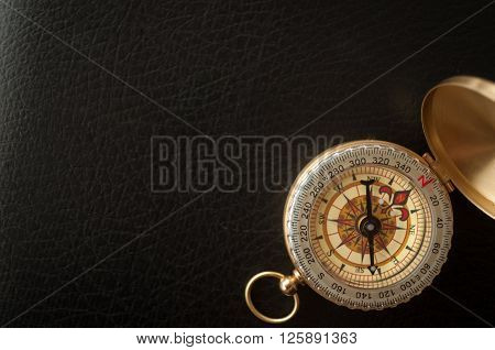 gold plated old compass on black leather