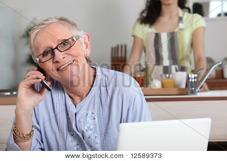Senior woman phoning in front of a laptop computer