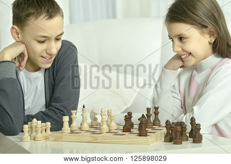 Little boy and little girl playing chess at home.Children playing chess