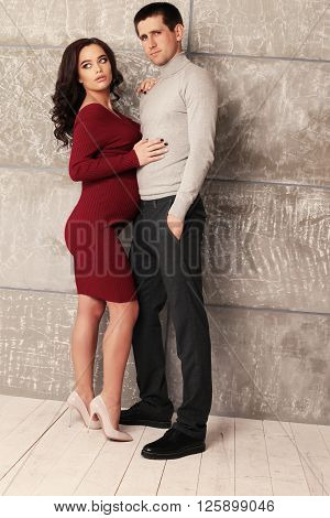 fashion studio photo of beautiful couple. pregnant beautiful woman with dark hair and handsome man in elegant clothes