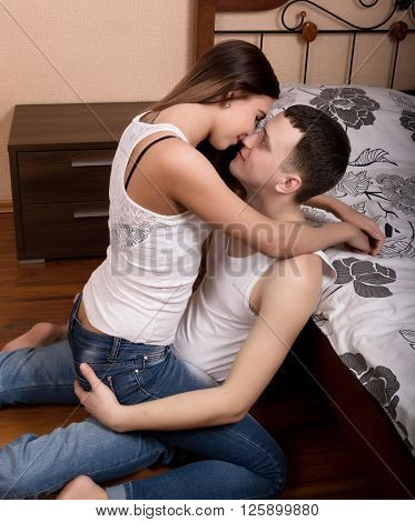 Fashion photo of two young beautiful lovers relax at the hotel on a bed, they are smiling, hugging and kissing. girl sits astride the man and kisses him.