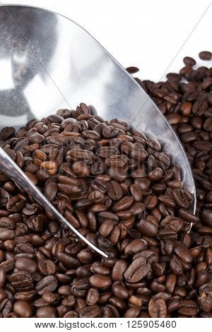 metal scooper on coffee beans isolated on white background