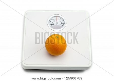 orange on weighing scale isolated on white background