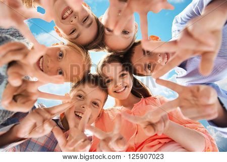 childhood, fashion, friendship and people concept - happy smiling children showing peace hand sign and standing in circle over blue sky and clouds background