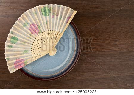 image of plate decorated with a chinese fan