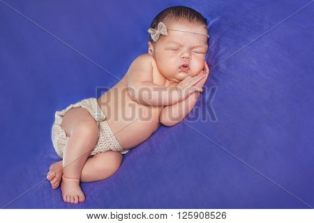 Peaceful sleep of a newborn child on a blue bed,a cute kid who wore a wreath on his head, sleeping sweetly tucked arms and legs on blue background