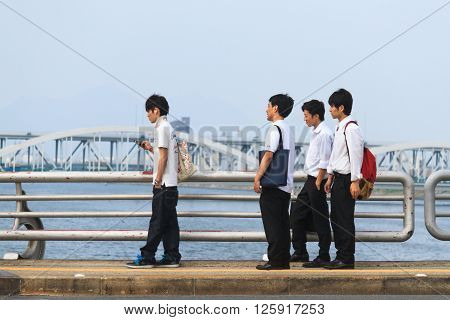 Hiroshima, Japan - July 10, 2014: Japanese young men stand on a bridge on Aioi river in Hiroshima, waiting for a redlight to turn green.
