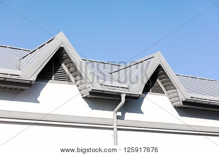Roof Gutter With Drainpipe On House Rooftop