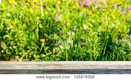 empty wooden board on a background of meadows with flowering herbs in the summer sunny day. Selective focus shallow depth of field. square photo. for product display montage