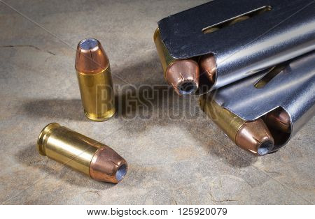 Hollow point bullets in cartridges and loaded magazines nearby