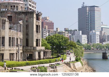 Hiroshima, Japan - July 10, 2014: The Atomic Bomb Dome (Hiroshima Peace Memorial) that was destroyed by the Atomic Bombing of Hiroshima in 1945. On the left the Aioi bridge (rebuilt), the actual target of the bombing, can be seen.
