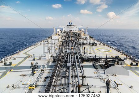 Deck of oil tanker in the blue ocean under sky - view from foremast.