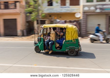 AGRA INDIA - 26TH MARCH 2016: A Tuk Tuk Rickshaw movong along a road in Agra during the day. Lots of people can be seen in it