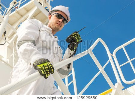 Engineer man in white workwear, goggles and helmet with VHF