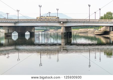 Hiroshima, Japan - July 10, 2014: Tram slowly crosses Aioi River via the rebuilt Aioi bridge, the official target of the Atomic Bombing in Hiroshima (