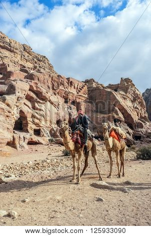 PETRA, JORDAN - NOVEMBER 22, 2007: Unidentified local Bedouin guided on camels near Royal tombs. The city of Petra was lost for over 1000 years. Now one of the Seven Wonders of the Word.