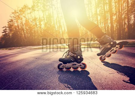 Teenage girl on roller skates at summer. Inline skates sport conceptual image.