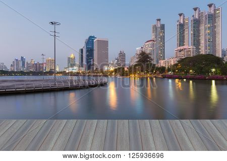 Opeing wooden floor, eflection view over Twin Suspension Bridge during sunset, landmark of Bangkok ThailandOffice building water front and reflection in public park view at night