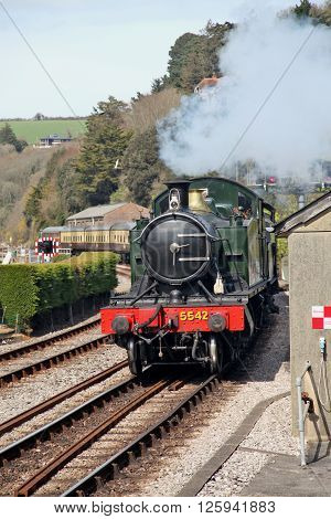 A steam train approaches Kingswear Devon loaded with holidaymakers