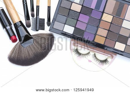 selective focus on professional makeup brushes red lipstick and eyelash and natural smoky and dark purple eyeshadows palette