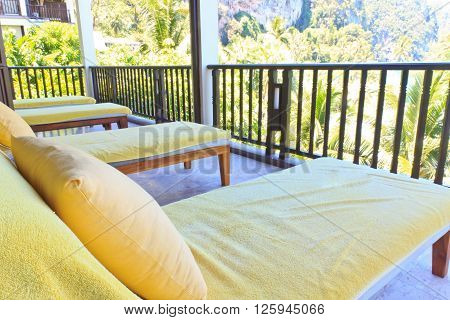 Yellow sunbeds on the balcony room in island