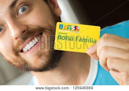 SAO PAULO, BRAZIL - CIRCA APRIL, 2016: Illustrative editorial of a man showing Bolsa Familia Card. Bolsa Familia is a social welfare program of the Brazilian government, part of the Fome Zero