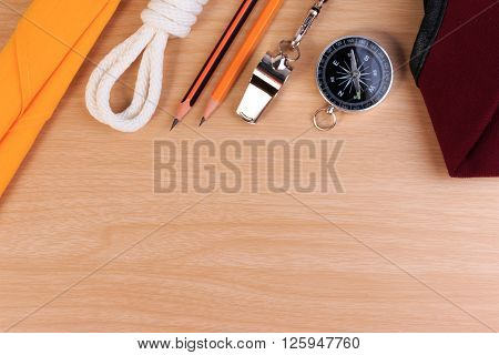 Orderliness White Scout Rope, Scarf, Whistle, Pencil, Compass And Red Beret On Wooden Table.