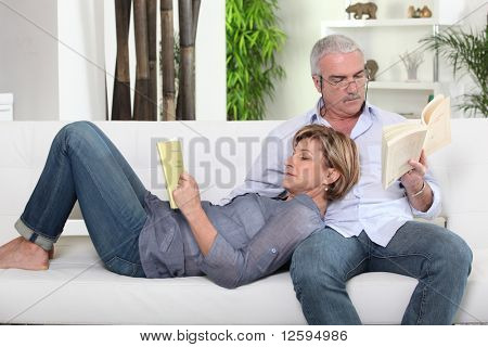 Senior couple relaxed reading a book