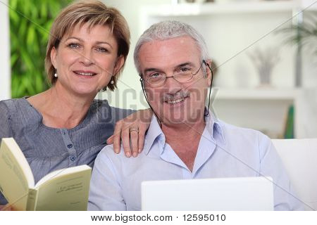 Senior woman reading a book near a senior man