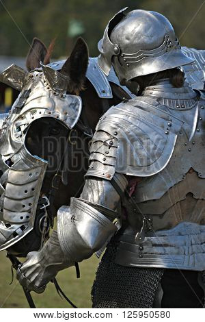 A knight prepares his horse for jousting battle.