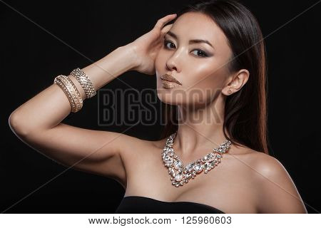 Beautiful young asian woman with elegant earrings and necklace. Shining evening make up