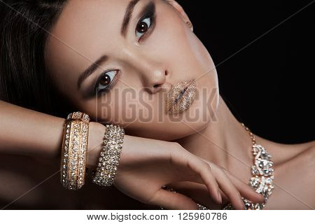 Beautiful sexy asian woman model with perfect makeup wearing luxury jewelry