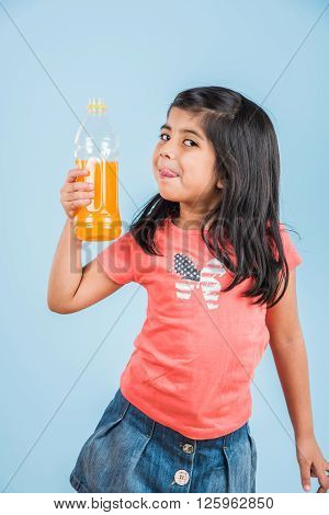indian girl with cold drink bottle, asian girl drinking cold drink in pet bottle, girl kid and cold drink, indian cute girl with mango or orange cold drink in plastic bottle, isolated on blue