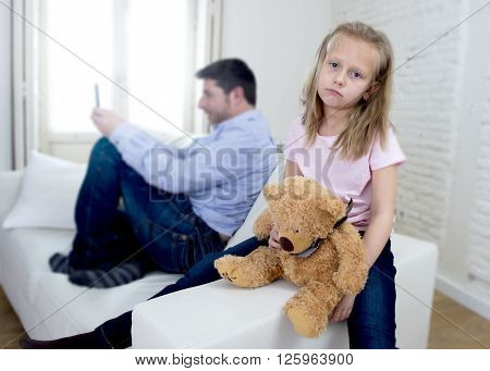 young internet addict father using mobile phone ignoring little sad daughter looking bored with teddy bear abandoned and disappointed with her dad in parent bad selfish behavior