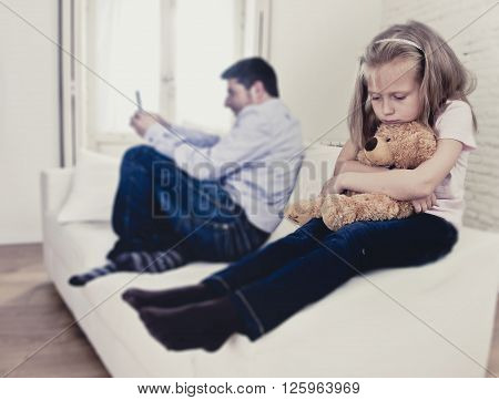 young internet addict father using mobile phone ignoring little sad daughter looking bored hugging teddy bear abandoned and disappointed with her dad in parent bad selfish behavior