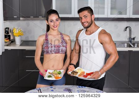 Fit Couple In The Kitchen, Holding Plates Of Food