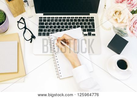 Topview of female hand writing in notepad on white desktop with notebook flowers perfume and other stuff