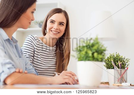Nice day. Charming positive glad girl sitting at the table and talking with her friend while expressing gladness
