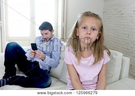 young internet addict father using mobile phone ignoring his little sad daughter looking bored lonely and depressed feeling abandoned and disappointed with her dad in parent bad selfish behavior
